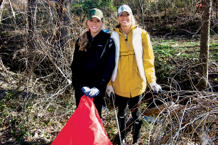 Two students from professor Robin Vaughan Hirshorn's Environmental Biology class pick up trash at the Sligo Creek site.