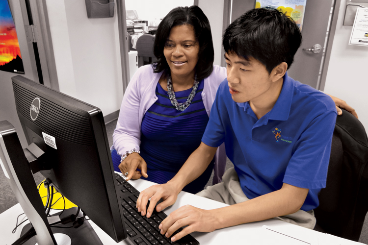 Karla Nabors supervises Steven Seo, who makes computer-generated certificates for students. Seo, who took classes in the College's Challenge Program, now works one day a week at Montgomery College and another day for the Montgomery County Sheriff's Office as part of SEEC Project SEARCH Montgomery.